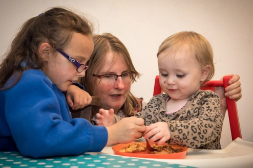 Girl helping toddler with food at the Cross Cafe